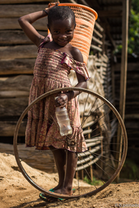 orphan girl with bicycle wheel